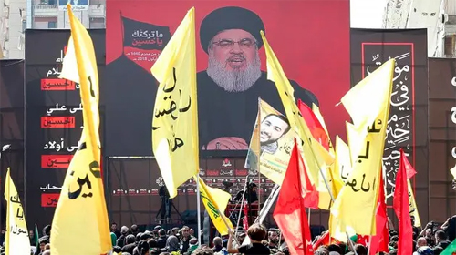 A rally of Hezbollah supporters with banner of their leader