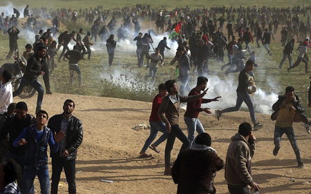 Palestinians run from teargas during the violence